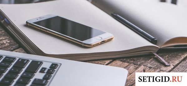 Белый айфон лежит на столе с ручкой и записной книжкой